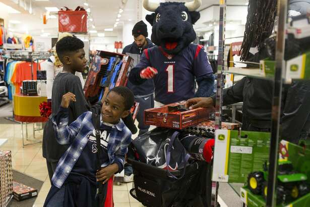 Jacob, 11, and LaKeith, 8, joke around while shopping with Toro and Jadeveon Clowney during a shopping spree at the Meyerland Palais Royal, Tuesday, Nov. 13, 2018 in Houston. After a fire destroyed their home, the children's grandmother Detra Harris has been living with her four grandchildren and another daughter and her two children in a small home, unsure of their future living situation. Palais Royal and the organization Kids' Meals wanted to do something special for the family after meeting them last year. Kids' Meals with their sponsor Palais Royal will give out 1,600 Thanksgiving meals this year to families.