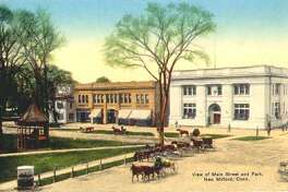 """This early 20th century view from the former Village Hardware at the corner of Main and Church streets shows the block between Bridge and Bank streets ravaged by the Great Fire of 1902 had been rebuilt several years later and looking much as it does today. What is referred to as the """"park,"""" for many years since known as the Village Green, was already graced at the time by the bandstand and lined by sidewalks as they are designed more than a century later. It would still be a few more years until travel was to be handled customarily by automobile, however, so parking along the plaza between the east and west sides of Main Street was arranged to accommodate horse and carriage. If you have a """"Way Back When"""" photograph to share, contact Deborah Rose at drose@newstimes.com or 860-355-7324."""