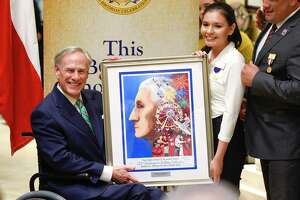 Texas Governor Greg Abbott and WBCA poster artist Jennifer Ramos pose for the media with a framed copy of this year's WBCA poster after Abbott was named Mr. South Texas for 2019 on Tuesday, Nov. 13, 2018, at Texas Community Bank.