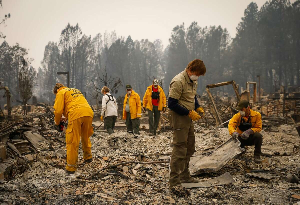 Search and rescue teams survey a property for remains at the Paradise Community Village Apartments in Paradise, California, on Tuesday, Nov. 13, 2018.