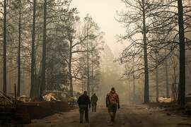 Yuba County Sheriffs walk back to their cars after discovering a fatality following the Camp Fire in Paradise, California, on Saturday, Nov. 10, 2018.
