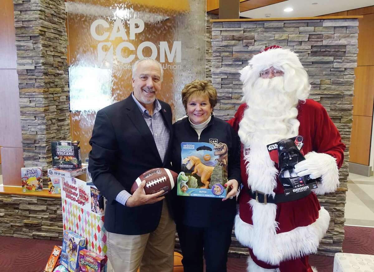 Lenny Ricchiuti, left, executive director of the Albany Police Athletic League and Paula Stopera, president and CEO of CAP COM Federal Credit Union, along with Santa take part in an event at CAP COM on Wednesday, Nov. 14, 2018, in Albany, N.Y. PAL held the event to announce the kickoff of their PAL Holiday Toy Drive. Drop boxes where new unwrapped gifts for boys and girls through age 12 will be located at all 11 CAP COM branches, Phillips Hardware and Albany Police headquarters. PAL also accepts gift cards, which make good gifts for the older children. PAL is looking to get 2,500 toys to needy children this holiday. PAL's Price Chopper/Market 32 Capital Holiday Lights will have their opening ceremony Thursday evening with Saturday, Sunday and Monday being walk-through events at the Capital Holiday Lights. The Capital Holiday Lights opens to vehicle traffic on Black Friday. Capital Holiday Lights is always looking for volunteers, especially electricians. (Paul Buckowski/Times Union)