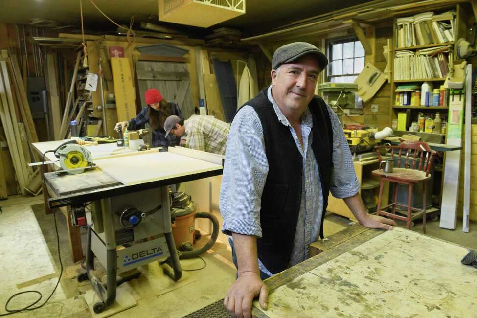 Chris Hacker poses in his workshop for his business with employees, Kelsea Adams, background left, and Owen Madden, on Wednesday, Oct. 17, 2018, in Albany, N.Y. The workshop and the home of Chris Hacker and Kate McKrell is one of the homes on the Holiday Home Tour this year. (Paul Buckowski/Times Union)