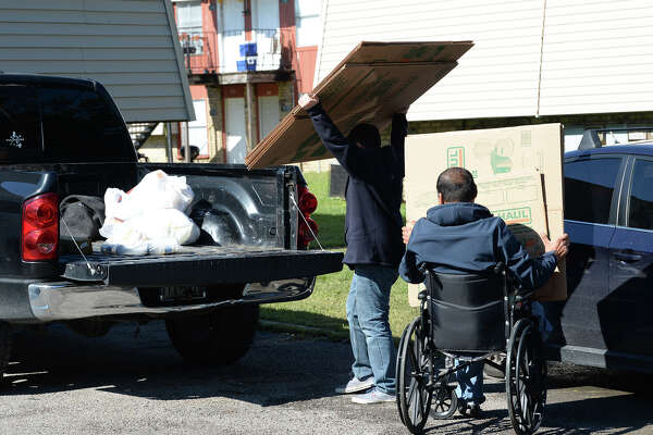Michael Villamil, 13, helps his father Aldrian Villamil move belongings from their Vidor apartment Wednesday after a fire damaged 16 units at the American Village Apartments Tuesday evening. Photo taken Wednesday, 11/14/18