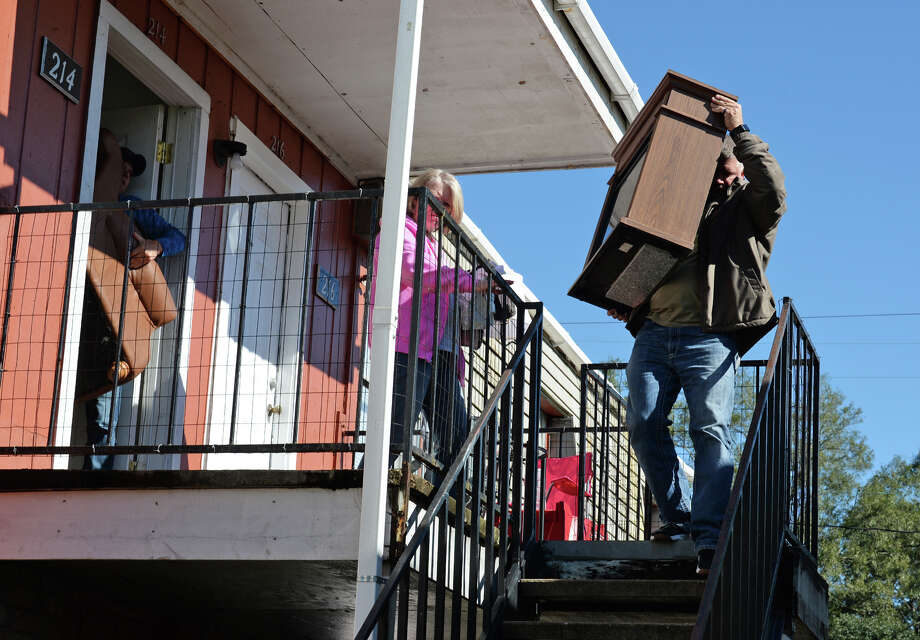 Jason Welch, right, hauls furniture Wednesday from his Vidor apartment which was damaged during a fire Tuesday night. Sixteen units at the American Village Apartment are now inhabitable from the fire. Mark Welch and Sandy Welch are also pictured. Photo taken Wednesday, 11/14/18 Photo: Guiseppe Barranco/The Enterprise / Guiseppe Barranco ?