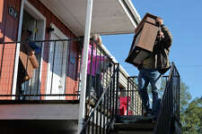 Jason Welch, right, hauls furniture Wednesday from his Vidor apartment which was damaged during a fire Tuesday night. Sixteen units at the American Village Apartment are now inhabitable from the fire. Mark Welch and Sandy Welch are also pictured. Photo taken Wednesday, 11/14/18