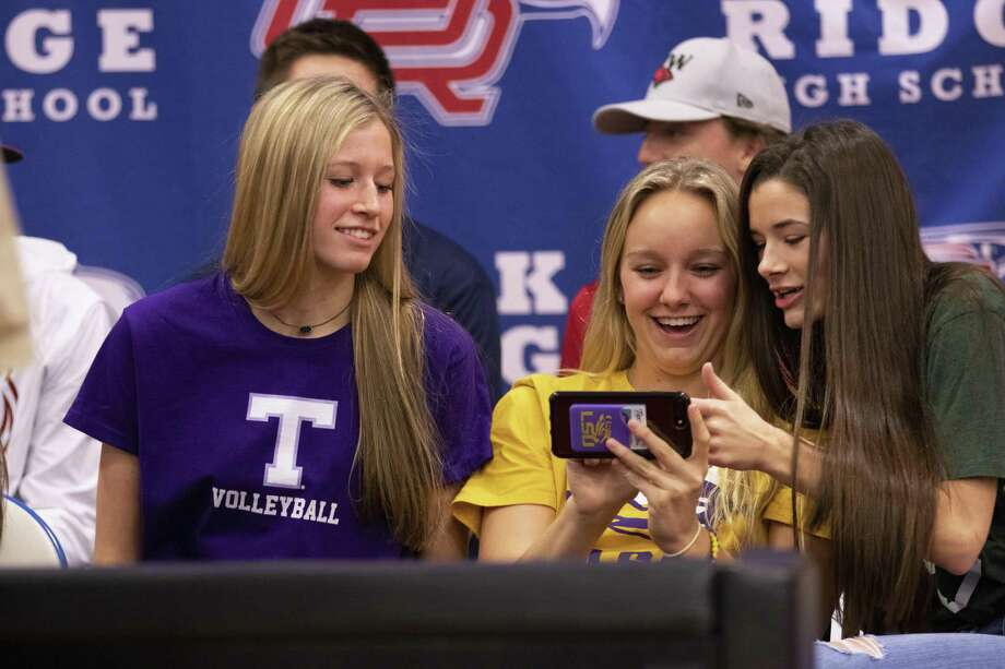 Oak Ridge seniors Brianna Rhodes, from left, Natalie Martin and Makenzie Arent check on a selfie they took just before signing commitments to separate colleges Wednesday, Nov. 14, 2018 at Oak Ridge High School in Conroe. Photo: Cody Bahn, Houston Chronicle / Staff Photographer / © 2018 Houston Chronicle