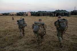 U.S. Army soldiers arrive at Base Camp Donna, one of multiple military bases being set up along the U.S.-Mexico border, in Donna, Texas, Nov. 8, 2018. Days after the midterm election, nearly 6,000 active-duty troops remain deployed from the Gulf Coast to Southern California, where they are putting up tents and stringing concertina wire to face a ragtag band that is still not near the border. (Tamir Kalifa/The New York Times)
