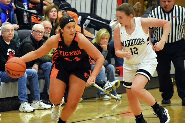 Edwardsville junior Kylie Burg, left, dribbles away from a defender after making a steal in the second quarter on Tuesday in Granite City.