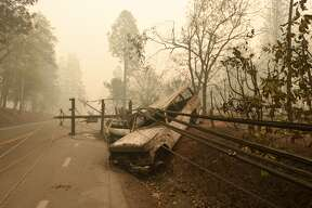 TOPSHOT - A fallen power line is seen on top of burnt out vehicles on the side of the road in Paradise, California after the Camp fire tore through the area on November 10, 2018. - Firefighters in California on November 10 battled raging blazes at both ends of the state that have left at least nine people dead and thousands of homes destroyed, but there was little hope of containing the flames anytime soon. So far, all nine fatalities were reported in the town of Paradise, in Butte County, where more than 6,700 buildings, most of them residences, have been consumed by the late-season inferno, which is now California's most destructive fire on record. (Photo by Josh Edelson / AFP) (Photo credit should read JOSH EDELSON/AFP/Getty Images)