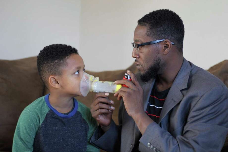 Robert Carmon, 7, of New Haven, suffers from asthma. His dad, Chaz Carmon, helps him avoid severe attacks. Photo: Steve Hamm / Conn. Health I-Team