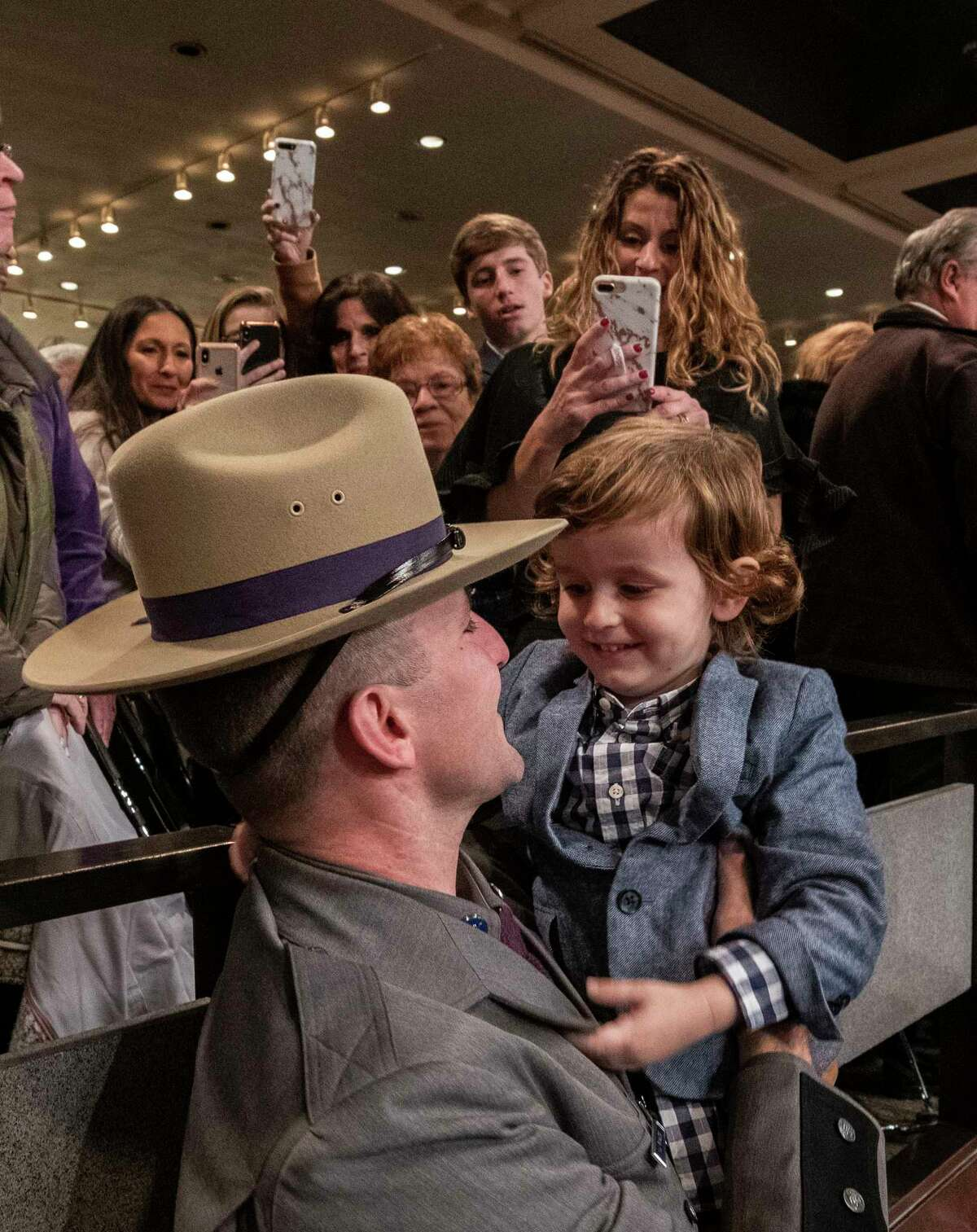 Trooper V.J. Rinaldo holds son Vincenzo, 3, of Canastota, N.Y. enjoys the moment with relatives after members of the 207th session of the Basic School at the New York State Police Academy graduated at the Empire Plaza Convention Center Wednesday Nov. 14, 2018 in Albany, N.Y. (Skip Dickstein/Times Union)
