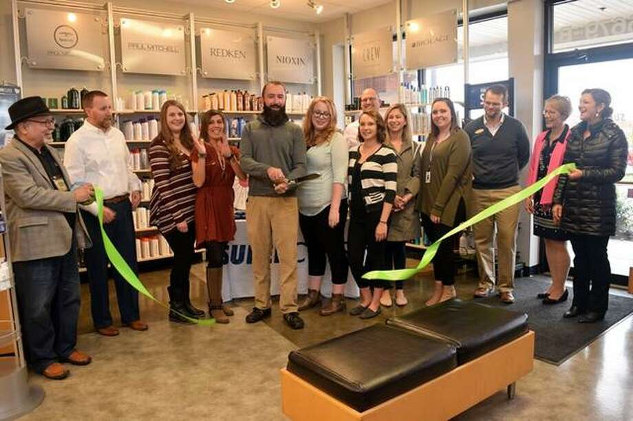 A ribbon-cutting ceremony at Supercuts in Edwardsville on Nov. 1 celebrates the transition to local ownership. Pictured are owner Alex Oliver and manager Kelly Schranz (both center) with staff and members of the Edwardsville/Glen Carbon Chamber of Commerce. Photo: For The Intelligencer