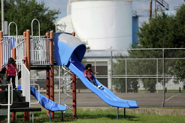 Elaine Martinez, 5, and her sister, Yadir, 3, play on the playground at Harman Park Community Center in the shadows of an oil refinery. Photos of a Houston neighborhood in the shadows of oil refineries on Tuesday, Sept. 29, 2015, in Houston. The EPA is requiring fence line monitoring to be done around refineries to measure the air quality.