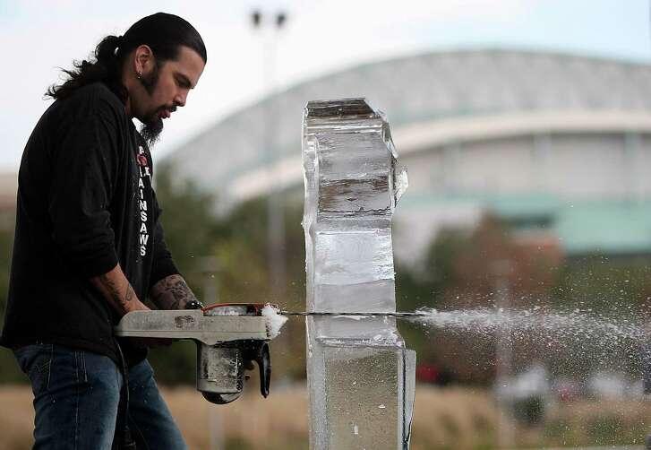 "The Reverend Butter, ""Rolando De La Garza"" carves ice."