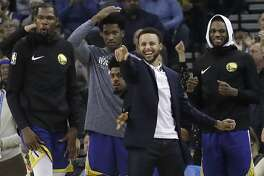 Injured Golden State Warriors guard Stephen Curry, foreground, celebrates with Kevin Durant, from left, Damian Jones, Quinn Cook and Alfonzo McKinnie during the second half of an NBA basketball game against the Atlanta Hawks in Oakland, Calif., Tuesday, Nov. 13, 2018. (AP Photo/Jeff Chiu)