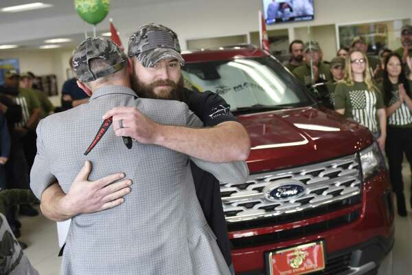 Stamford Ford Lincoln President Dominic Franchella presents U.S. Marine Ret. Cpl. Andrew Burns with a new car during the Veterans Day car giveaway at Stamford Ford Lincoln in Stamford, Conn. Monday, Nov. 12, 2018. The dealership gave away cars to U.S. Marine Ret. Cpl. Andrew Burns and U.S. Army Ret. Col. Vanessa Benson, leader of Ford Military and Veteran Initiatives.