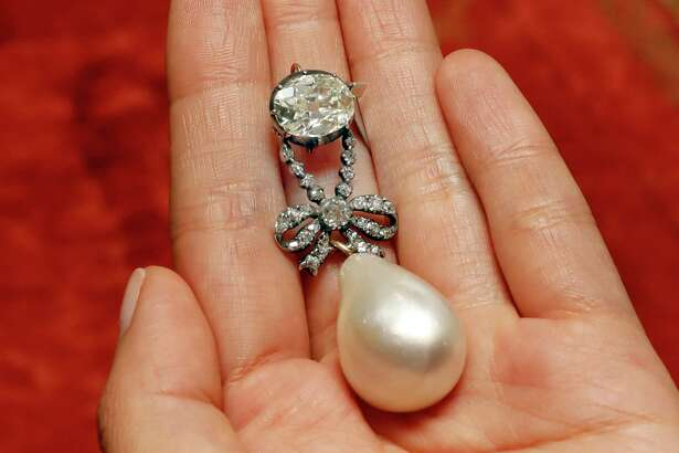 """FILE - In this Friday, Oct. 12, 2018 file photo, the Queen Marie Antoinette Pearl and diamond pendant, from the 18th century, is displayed at Sotheby's, in New York. A large, drop-shaped natural pearl pendant sold for a hammer price of $32 million at an auction of jewelry that once belonged to French queen Marie Antoinette, which Sotheby's is calling a record price for a pearl at auction. The """"Queen Marie Antoinette's Pearl,"""" a diamond-and-pearl pendant, was among the highlight offerings on the block at the Sotheby's sale of jewelry from the Bourbon-Parma dynasty on Wednesday, Nov. 14."""