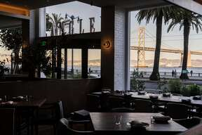 The Bay Bridge is seen through the windows of the main dining room inside Angler along the Embarcadero in San Francisco, Calif. Wednesday, Nov. 7, 2018.