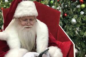 Santa Claus at The Galleria checks to see if his reindeer have texted him back yet.