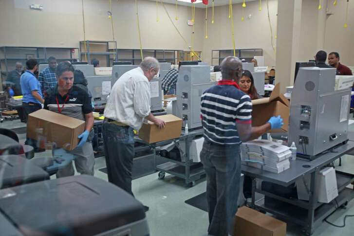 Election workers recount votes during the Florida midterm election recount on Tuesday, Nov. 13, 2018, at the Broward Supervisor of Elections office in Lauderhill, Fla.