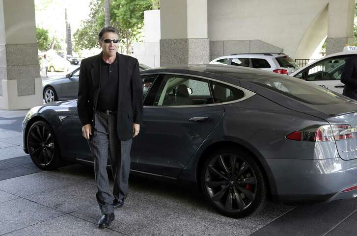 Texas Gov. Rick Perry walks over to talk to reporters after driving up in a Tesla Motors Type S electric car in Sacramento, Calif.