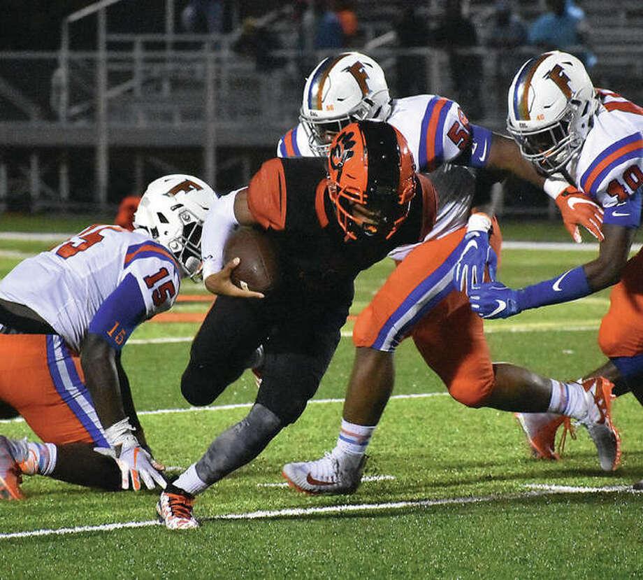 Edwardsville quarterback Kendall Abdur-Rahman tries to split through the East St. Louis defense during a game in the regular season. Photo: Matt Kamp/Intelligencer