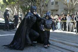 """Miles Scott, dressed as Batkid, right, walks with Batman before saving a damsel in distress in San Francisco, Friday, Nov. 15, 2013. San Francisco turned into Gotham City on Friday, as city officials helped fulfill Scott's wish to be """"Batkid."""" Scott, a leukemia patient from Tulelake in far Northern California, was called into service on Friday morning by San Francisco Police Chief Greg Suhr to help fight crime, The Greater Bay Area Make-A-Wish Foundation says. (AP Photo/Jeff Chiu)"""
