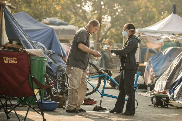 Whitney Moses hand out smoke masks to Tim Green, an ex-Marine at a homeless encampment near Home Depot at Alameda Ave and High Street on Monday, Nov. 12, 2018, in Oakland, Calif.