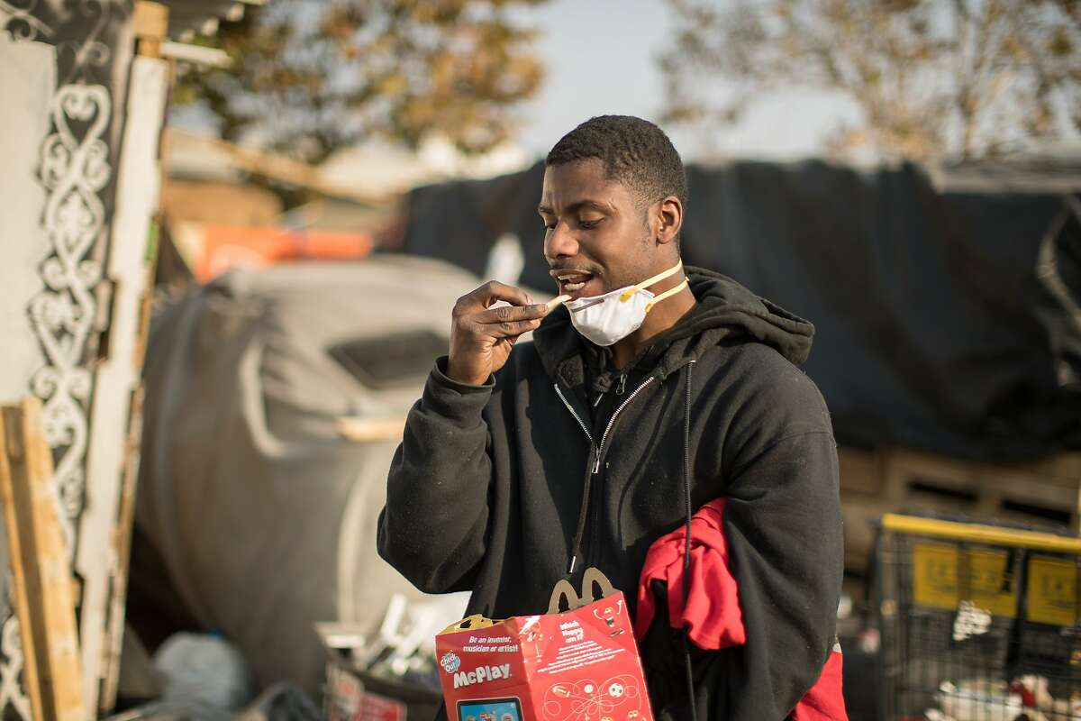 Jonathan Knowell eats fries after receiving a mask from Cassandra Williams and Whitney Moses at a homeless encampment near Home Depot at Alameda Ave and High Street on Monday, Nov. 12, 2018, in Oakland, Calif.