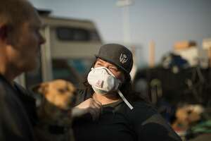 Cassandra Williams handing out smoke masks to ex-Marine Tim Green who now must live at a homeless encampment near Home Depot at Alameda Ave and High Street on Monday, Nov. 12, 2018, in Oakland, Calif.