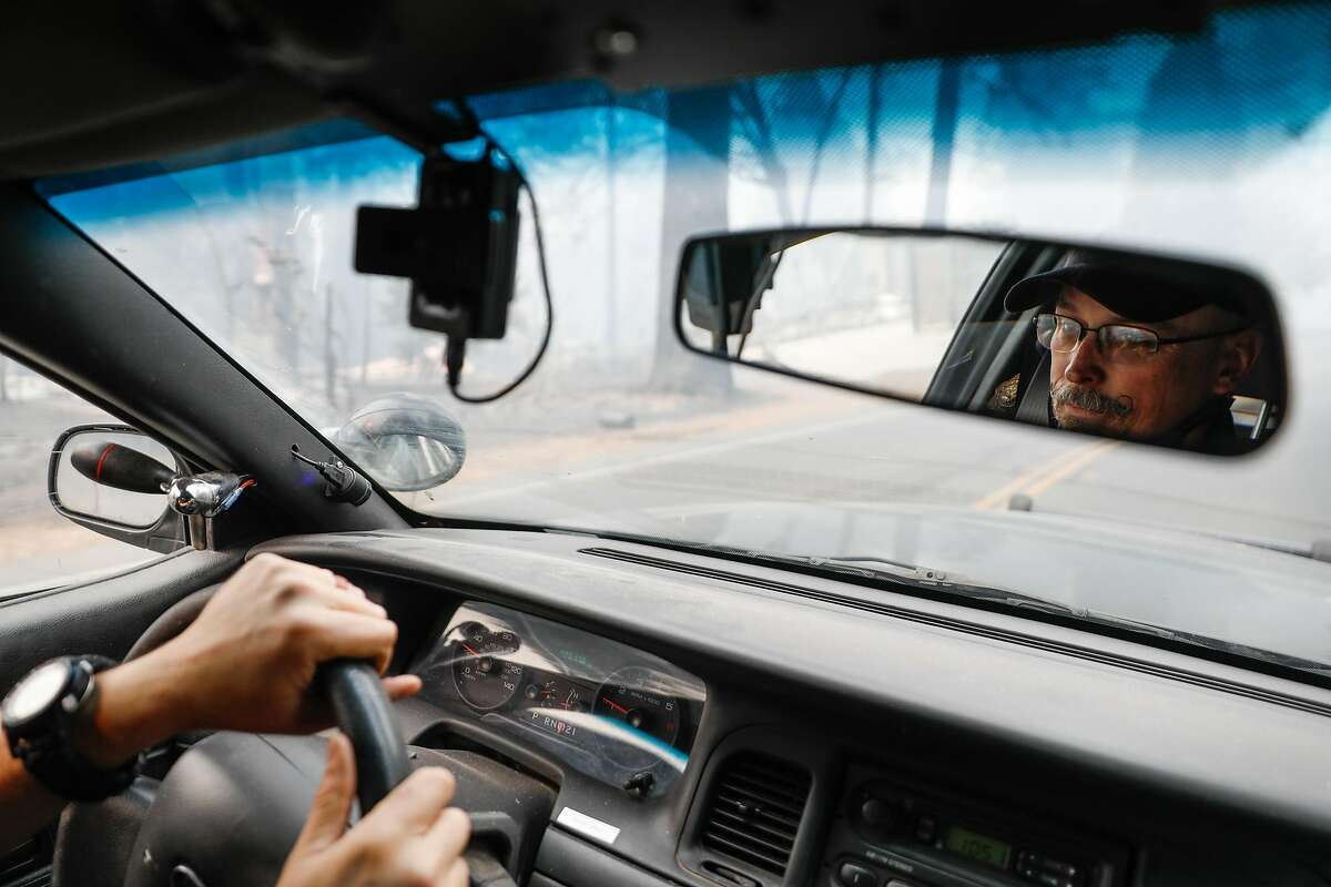 Sgt. Robert Pickering is seen in the mirror while patrolling following the Camp Fire in Paradise, California, on Wednesday, Nov. 14, 2018.