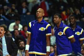 Earvin Magic Johnson #32 of the Los Angeles Lakers stands between teammates Kareem Abdul-Jabbar, left, and Orlando Woolridge, right against the Washington Bullets circa 1988 during an NBA basketball game at the Capital Center in Landover, Maryland. Johnson played for the Lakers from 1979 - 1991 and 1996.