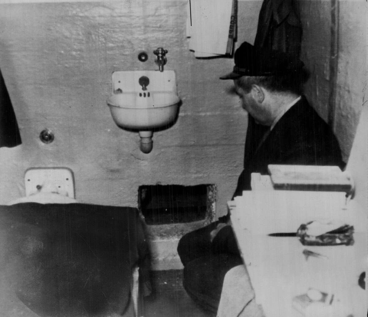 Where the Alcatraz prison break started: A prison guard kneels by hole in Frank Morris' cell.