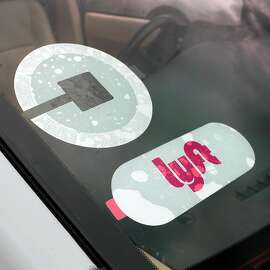 Uber and Lyft decals on a car near the airport Wednesday June 27, 2018 in Colonie, NY.  (John Carl D'Annibale/Times Union)