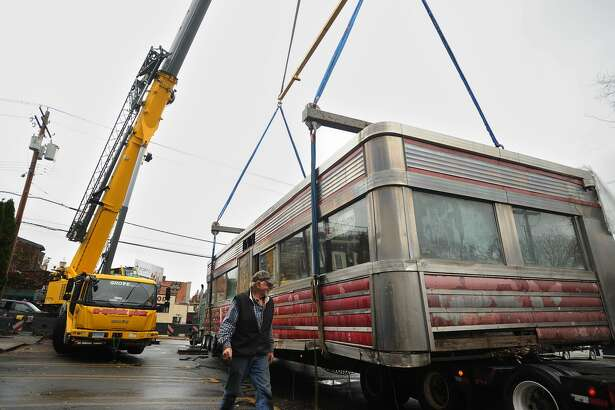 The Milford Diner is loaded on to a flatbed truck for transport from its location on New Haven Avenue in downtown Milford on Tuesday. The 1946 diner is travelling to Kokomo, Indiana, where it will be restored and reopen for business.