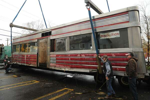 The Milford Diner is loaded on to a flatbed truck for transport from its location on New Haven Avenue in downtown Milford Tuesday. The 1946 diner is travelling to Kokomo, Ind., where it will be restored and reopen for business.