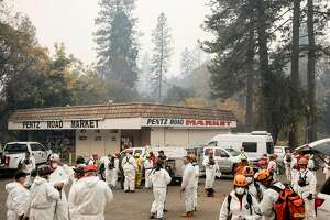 Search and Rescue teams as well as forensics and archaeologists gather near Pentz Road Market before heading out to search through the rubble of homes for victims in Paradise, Calif. Wednesday, Nov. 14, 2018 after the Camp Fire ripped through the entire town.