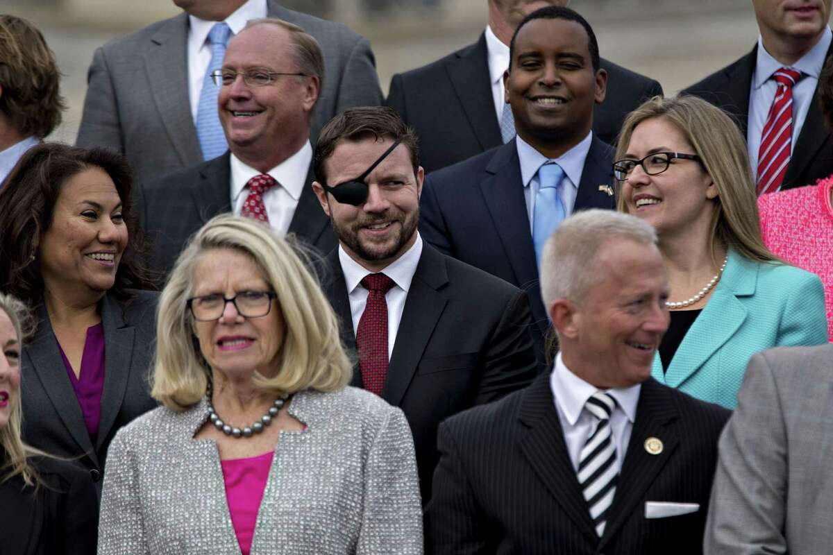 Representative-elect Dan Crenshaw, a Republican from Texas, center, and Representative-elect Jennifer Wexton, a Democrat from Virginia, right, wait for a group photo with the 116th Congress outside the U.S Capitol in Washington, D.C., U.S., on Wednesday, Nov. 14, 2018. Congress returns to work this week with Democrats and Republicans promising to work together to avert a partial government shutdown and pass a handful of other bills, though President Donald Trumps demand to fund his border wall could blow up their plans. Photographer: Andrew Harrer/Bloomberg