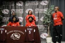 Robert Adams, right, speaks while his son Jordyn Adams, center, and Devon McCain sign to play basketball at Austin Peay during a ceremony at Silsbee High School on Wednesday. Photo taken Wednesday 11/14/18 Ryan Pelham/The Enterprise