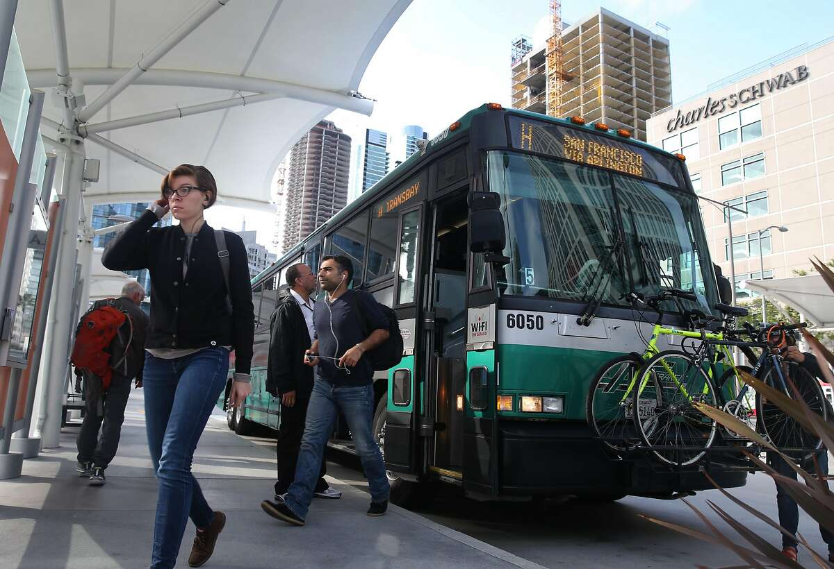 Passengers exit an AC Transit bus after commuting from the East Bay in San Francisco, Calif.