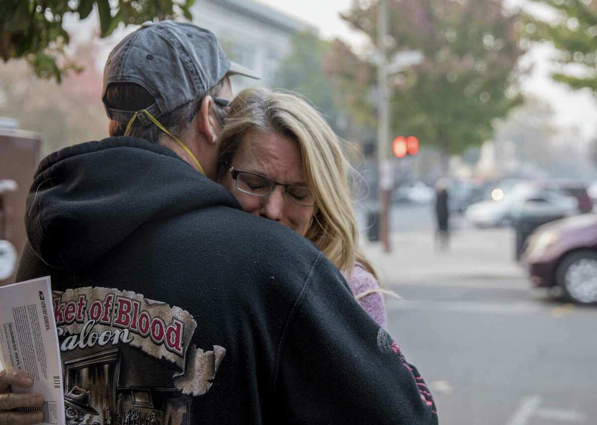 Bill Wilson comforts his wife, Charlotte Wilson, while in line outside of the Chico Post Office in Chico, Calif. Wednesday, Nov. 14, 2018 to change their address after losing their Paradise home in the Camp Fire.