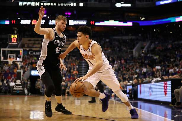 PHOENIX, AZ - NOVEMBER 14: Devin Booker #1 of the Phoenix Suns drives the ball past Davis Bertans #42 of the San Antonio Spurs during the first half of the NBA game at Talking Stick Resort Arena on November 14, 2018 in Phoenix, Arizona. NOTE TO USER: User expressly acknowledges and agrees that, by downloading and or using this photograph, User is consenting to the terms and conditions of the Getty Images License Agreement. (Photo by Christian Petersen/Getty Images)