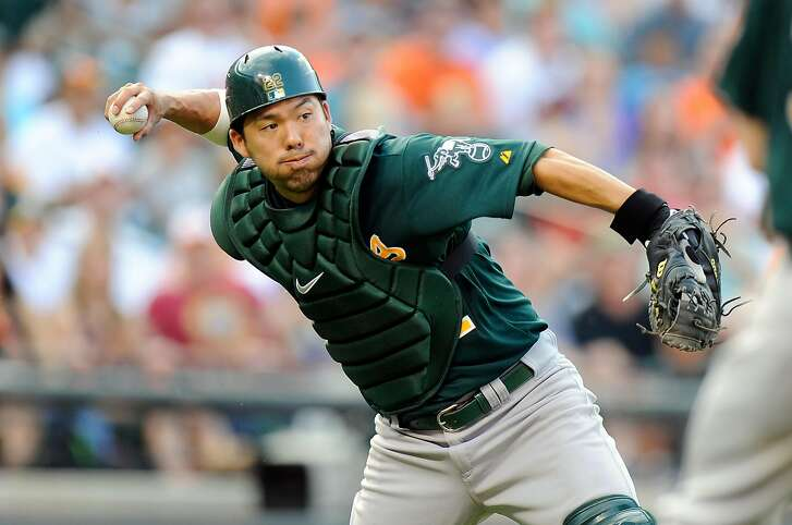 BALTIMORE, MD - AUGUST 24:  Kurt Suzuki #22 of the Oakland Athletics fields a bunt and throws to first base in the eighth inning against the Baltimore Orioles at Oriole Park at Camden Yards on August 24, 2013 in Baltimore, Maryland.  (Photo by Greg Fiume/Getty Images)