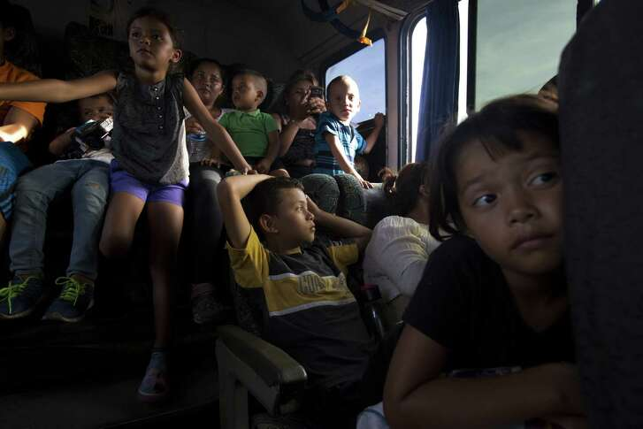 Children squeeze onto laps and share seats on a bus that was donated to transport some of the families with small children to the next stop, as a thousands-strong caravan of Central Americans continues its slow journey toward the U.S. border in Niltepec, Oaxaca state, Mexico, Tuesday, Oct. 30, 2018. The migrant caravan slowly advancing through southern Mexico is demanding that the Mexican government help its 4,000-some members reach Mexico City even as a second smaller group of Central American migrants entered the country, presumably with the intention of joining it.