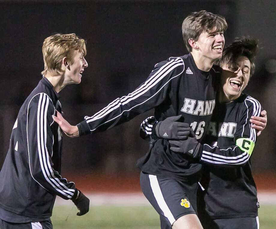 Hand's Lucas Vest (21), Greyson McGeary (16) and Thomas LaTorre (4) celebrate their CIAC Class L semifinal win over Wethersfield on Wednesday night in Naugatuck. Photo: John Vanacore / For Hearst Connecticut Media / (C)John H.Vanacore