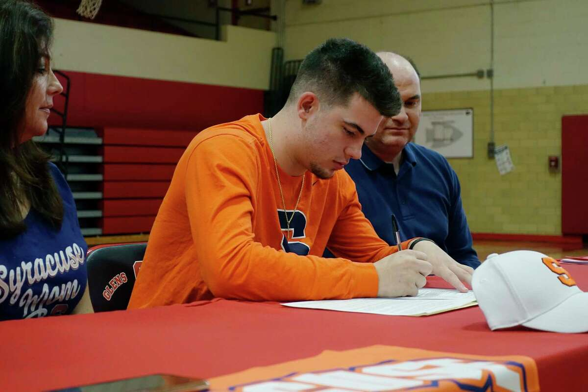 Glens Falls High School basketball player, Joseph Girard III, center, signs his Letter of Intent to play for Syracuse University as his mother, Arleen and father Joe, Jr., join him for he signing on Wednesday, Nov. 14, 2018, in Glens Falls, N.Y. (Paul Buckowski/Times Union)