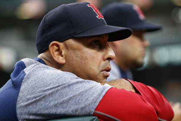 FILE - In this July 24, 2018, file photo, Boston Red Sox manager Alex Cora leans against the dugout rail during the second inning of the team's baseball game against the Baltimore Orioles in Baltimore. The Red Sox rewarded Cora for winning a World Series in his first year with the team, giving him a new contract that includes an additional guaranteed year through the 2021 season, in a deal announced Wednesday, Nov. 14. (AP Photo/Patrick Semansky, File)