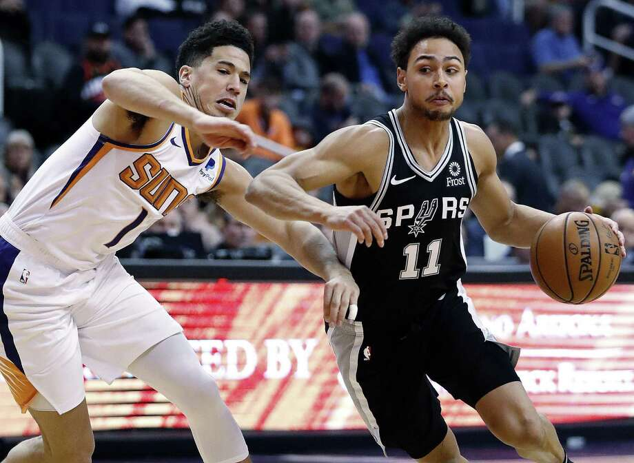 Spurs guard Bryn Forbes drives on Suns guard Devin Booker. Forbed had 13 points, but none in the second half. Photo: Matt York /Associated Press / Copyright 2018 The Associated Press. All rights reserved