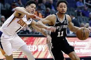 Spurs guard Bryn Forbes drives on Suns guard Devin Booker. Forbed had 13 points, but none in the second half.